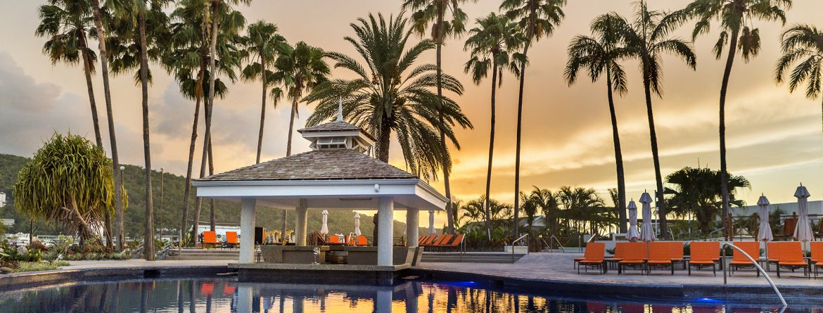 Moon Palace Jamaica pool at sunset with palm trees and orange sky.