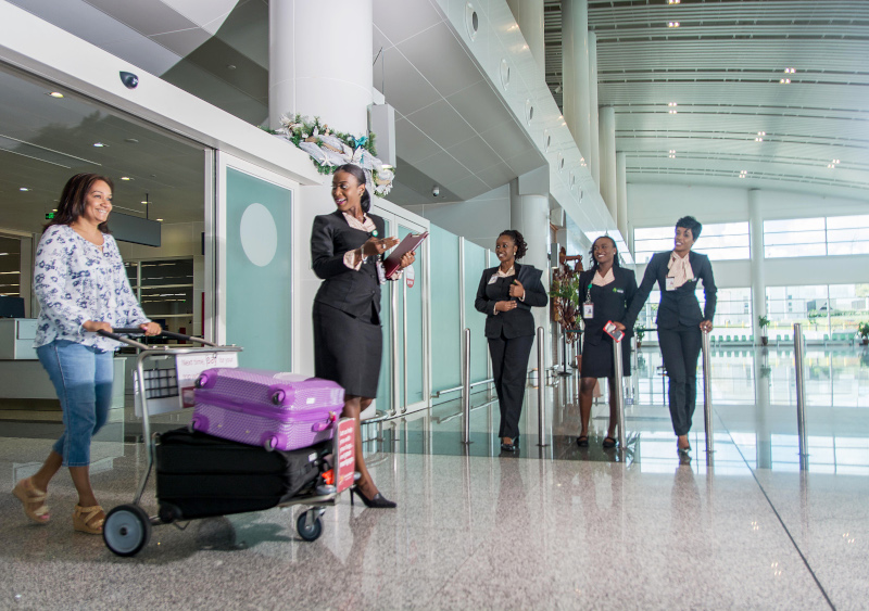 VC Bird International Airport manage by Antigua and Barbuda Airport Authority. Female employees greeting a woman traveler pushing luggage.
