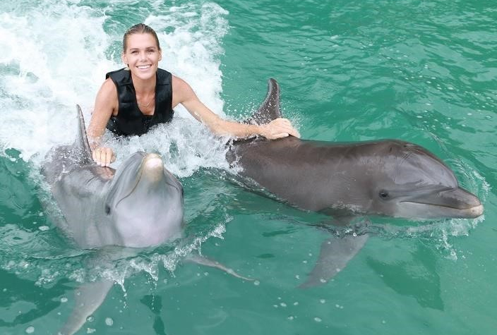 Dolphin Cove Jamaica photo of a woman getting a pull by two dolphins in the water.