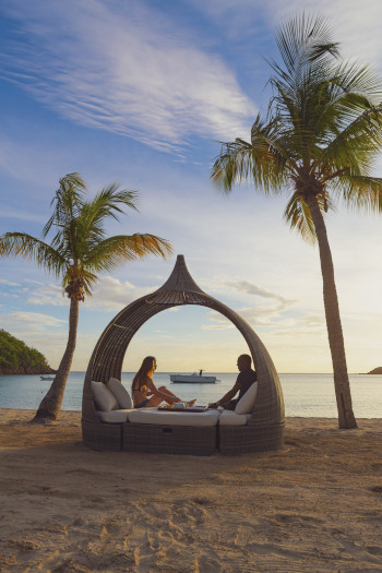 Carlisle Bay Resort Antigua couple sitting on a wicker chair with cushions on the beach.
