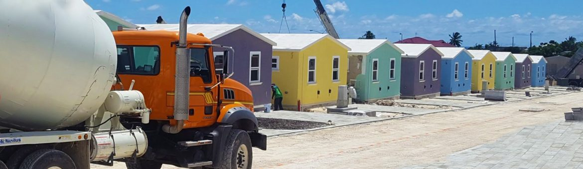 Ready-Mix Limited Barbados cement truck at a new home construction site with a row of colorful houses.