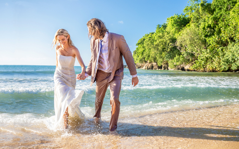 Couples San Souci Jamaica, a woman and man in wedding attire playing in the beach surf.