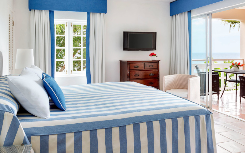 Couples San Souci Jamaica, a vibrant white and blue bedroom interior with a beach view visible in the corner beyond the patio.